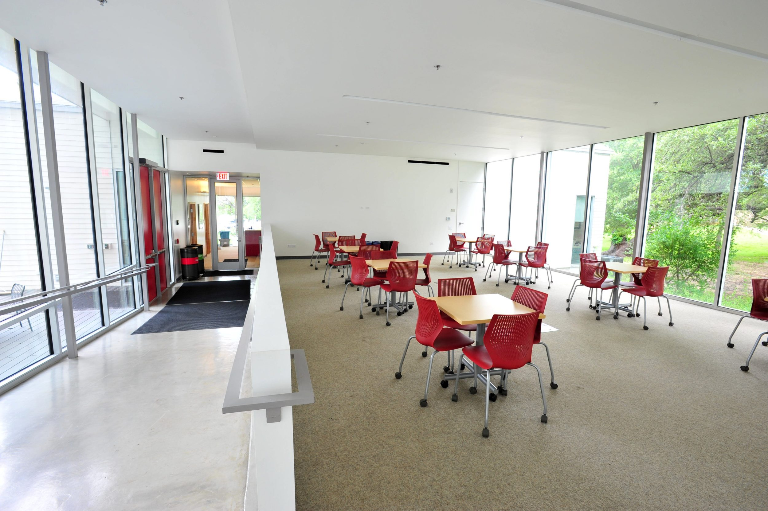 Image of the St. Edward's University Chapel Renovation Common Area including tables, chairs and hallway