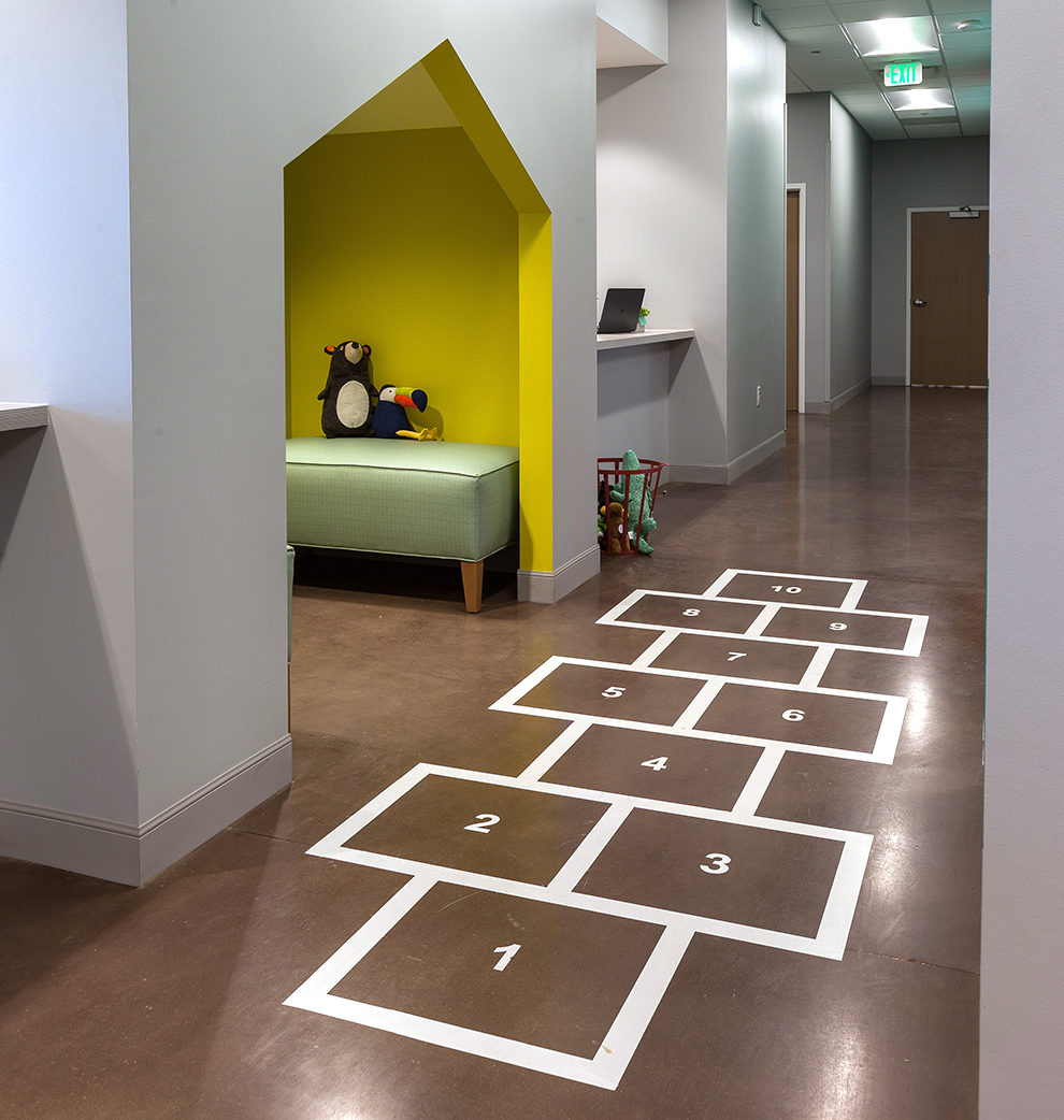 Image of the Treehouse Pediatrics hallway with hopscotch on the floor as well as a reading nook for patients.